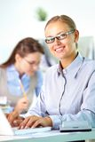 Happy secretary. Portrait of pretty secretary looking at camera while working Royalty Free Stock Photo