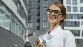 Businesswoman holding tablet in front of corporation. Happy and self-confident young dark hair caucasian businesswoman, in a white blouse and stylish glasses, is stock video