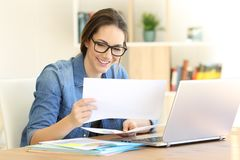 Happy self employed cheching files at home. Happy self employed cheching paper files on a table at home Royalty Free Stock Images