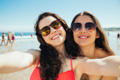 Happy selfie friends on the beach. Funny female friends on vacation taking selfies on the beach with a smart phone Stock Photography