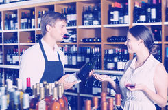 Happy seller man giving sample taste of wine. Happy seller men wearing apron giving sample taste of wine in glass to women customer in wine store Royalty Free Stock Photography