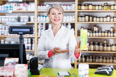 Happy seller recommending skin care products. In specialized shop Stock Photo