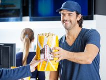 Happy Seller Selling Popcorn To Man At Concession Stock Images