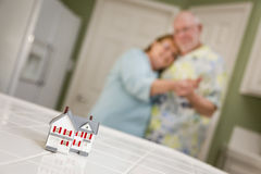 Senior Adult Couple Gazing Over Small Model Home on Counter Royalty Free Stock Photo