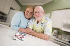 Senior Adult Couple Gazing Over Small Model Home on Counter Royalty Free Stock Images