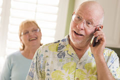 Senior Adult Husband on Cell Phone with Wife Behind Royalty Free Stock Images