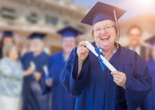 Happy Senior Adult Woman In Cap and Gown At Outdoor Graduation C. Eremony Stock Images