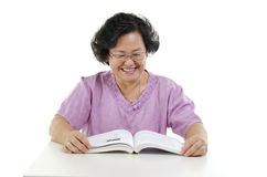 Happy Senior adult woman reading book. Portrait of wise Asian senior adult woman reading book, isolated on white background Stock Photo