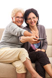 Happy senior and adult women using a remote Stock Photo