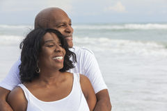 Happy Senior African American Couple on Beach. Happy romantic senior African American men and women couple on a deserted tropical beach royalty free stock image