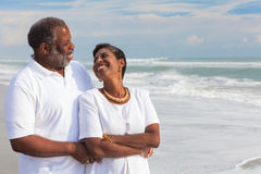 Happy Senior African American Couple on Beach. Happy romantic senior African American men and women couple looking at each other on a deserted tropical beach Stock Images