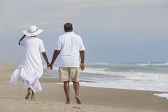 Happy Senior African American Couple Man Woman on Beach. Happy romantic senior African American men and women couple walking holding hands on a deserted tropical Stock Photos