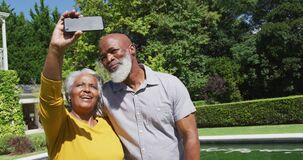 Happy senior african american couple using smartphone taking selfie by swimming pool in sunny garden