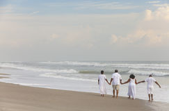 Happy Senior African American Couples Men Women on Beach. Rear view of happy romantic senior African American men and women couples walking holding hands on a Royalty Free Stock Photography