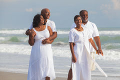 Happy Senior African American Couples Men Women on Beach. Happy romantic senior African American men and women couples walking on a deserted tropical beach Royalty Free Stock Image
