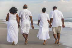 Happy Senior African American Couples Men Women on Beach. Happy romantic senior African American men and women couples walking holding hands on a deserted Stock Photo