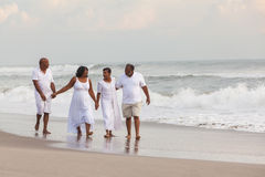 Happy Senior African American Couples Men Women on Beach. Happy romantic senior African American men and women couples walking holding hands on a deserted Stock Photos
