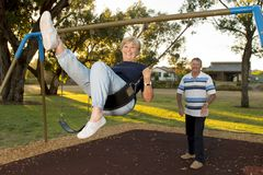 Happy senior American couple around 70 years old enjoying at swing park with husband pushing wife smiling and having fun Stock Photography