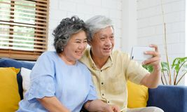 Happy senior asian couple taking selfie at home living room, active senior people in happy moment, casual retirement people with. Technology and lifestyle royalty free stock photography