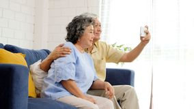 Happy senior asian couple taking selfie at home living room, active senior people in happy moment, casual retirement people with. Technology and lifestyle royalty free stock images
