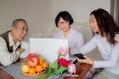 Daughter and senior parents using laptop at home. stock photos