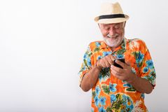 Happy senior bearded tourist man smiling and giggling while using phone. Studio shot of happy senior bearded tourist man smiling and giggling while using mobile stock image