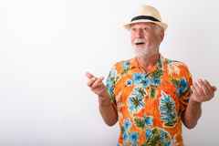 Happy senior bearded tourist man smiling while looking surprised with both arms raised. Studio shot of happy senior bearded tourist man smiling while looking royalty free stock images