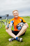 Happy senior bicyclist. Happy active senior bicyclist sitting on grass and resting stock photos