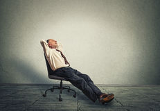 Happy senior business man relaxing in empty office Stock Photo