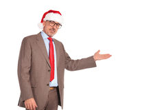 Happy senior business man wearing santa claus hat presenting Stock Photos