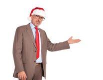 Happy senior business man wearing santa claus hat presenting Stock Photos