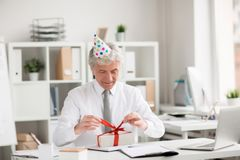 Birthday of director. Happy senior businessman in birthday-cap untying ribbon on top of gift-box in office Royalty Free Stock Photo