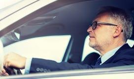 Happy senior businessman driving car stock images
