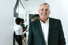Happy senior businessman in office corridor royalty free stock images
