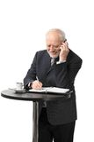 Happy senior businessman on the phone. Portrait of happy senior businessman standing at coffee table talking on mobile phone, isolated on white Royalty Free Stock Photography