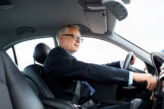 Happy senior businessman starting car and driving. Transport, business trip and people concept - happy senior businessman starting car and driving Royalty Free Stock Photo