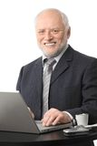 Happy senior businessman using computer. Portrait of happy senior businessman using laptop on coffee table, eye contact, white background Royalty Free Stock Image