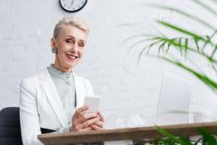 Happy senior businesswoman using smartphone at workplace. With laptop stock photo