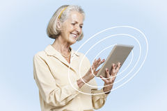 Happy senior businesswoman using tablet PC against clear blue sky Royalty Free Stock Photography