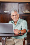 Happy senior in café with laptop computer Stock Image