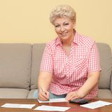Happy senior calculating her debts Stock Images