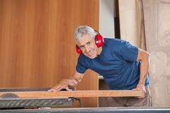 Happy Senior Carpenter Cutting Wood With Tablesaw Royalty Free Stock Photos