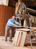 Happy Senior Carpenter Using Bandsaw Royalty Free Stock Photography