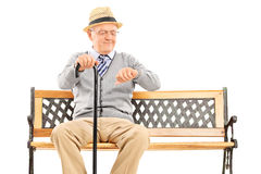 Happy senior checking the time seated on a bench Stock Images