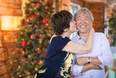 Happy Senior Chinese Couple Kissing In Front of Decorated Christ Stock Photo