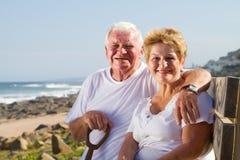 Happy senior couple. Sitting on beach bench Royalty Free Stock Photos
