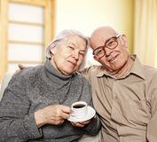 Happy senior couple. Drinking coffee at home Stock Image