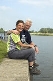 Happy senior couple. Relaxing and enjoying the sun, sitting at the harbour royalty free stock images