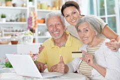 Happy senior couple with adult daughter using laptop Royalty Free Stock Photography