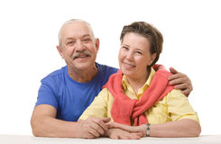 Happy senior couple against white background. Close-up of a happy senior couple. Hugging and looking at camera Royalty Free Stock Photos